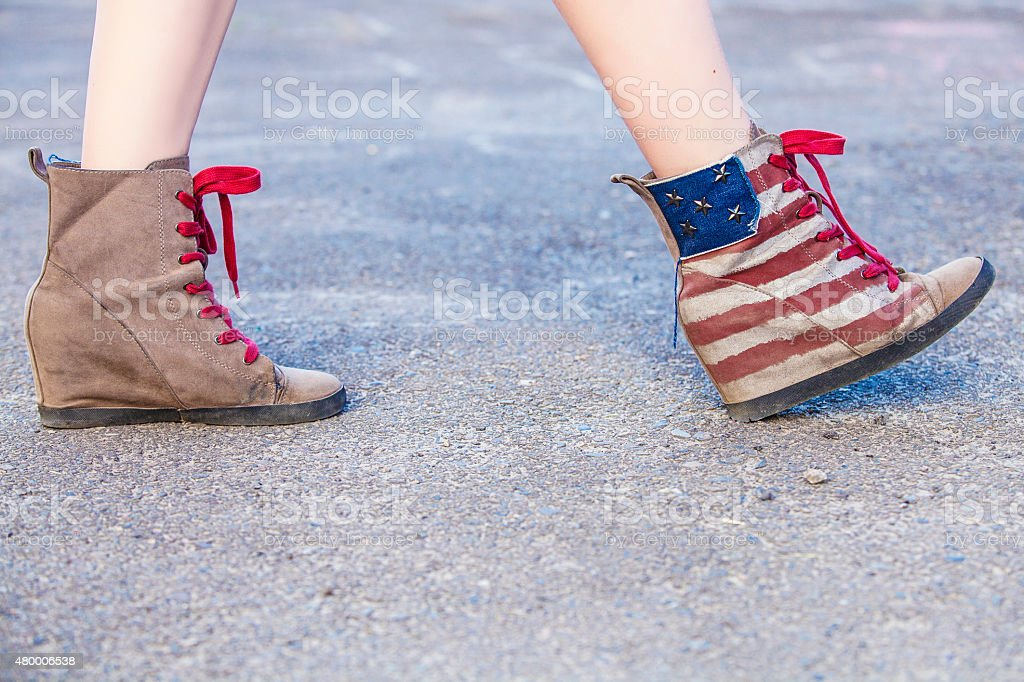 Female legs in sneakers with the design stock photo