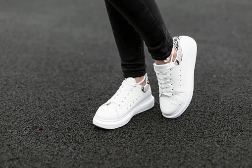 Female legs in stylish black jeans in white leather sneakers with snake pattern on the asphalt in the city. Young women on a walk. Fashionable women's shoes. New collection. Close-up.