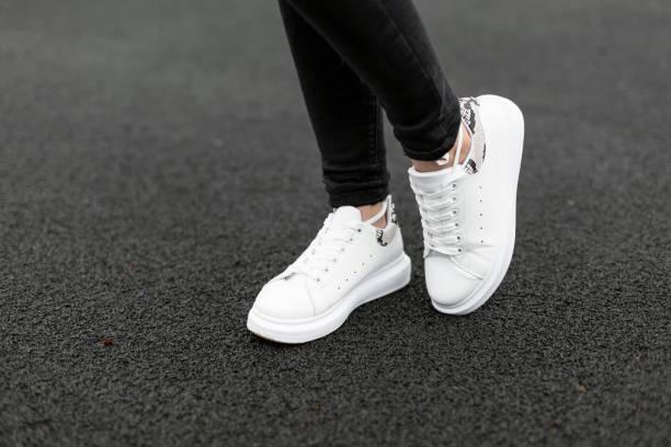 vrouwelijke benen in stijlvolle zwarte jeans in wit lederen sneakers met slang patroon op het asfalt in de stad. jonge vrouwen op een wandeling. modieuze damesschoenen. nieuwe collectie. close-up. - zwarte spijkerbroek stockfoto's en -beelden