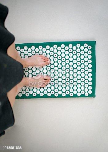 istock Female legs on a needle applicator, foot massage. Needle Kuznetsov acupressure applicator. 1218581636