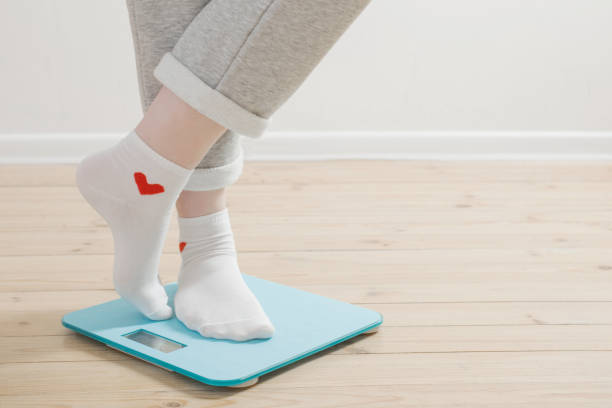 female legs on electronic scales on a wooden floor stock photo