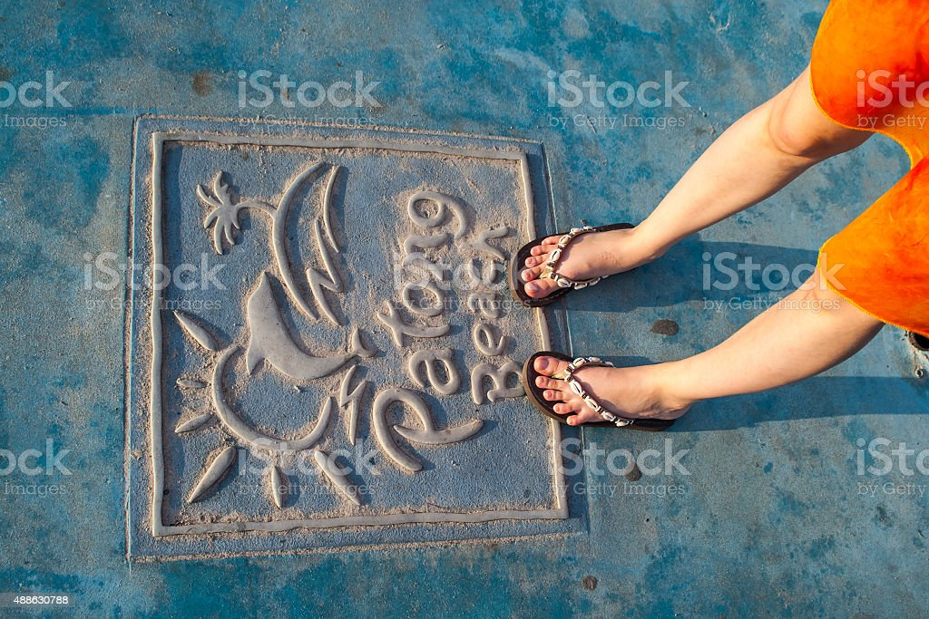 female legs standing on the plate with the Patong Beach name stock photo
