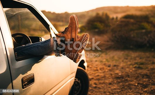 Woman's boots hanging out of an old car window on a country road trip