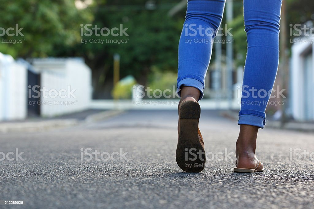 Female legs walking on the road stock photo