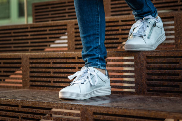 Female legs wearing jeans and white sneakers walking down on stairs stock photo