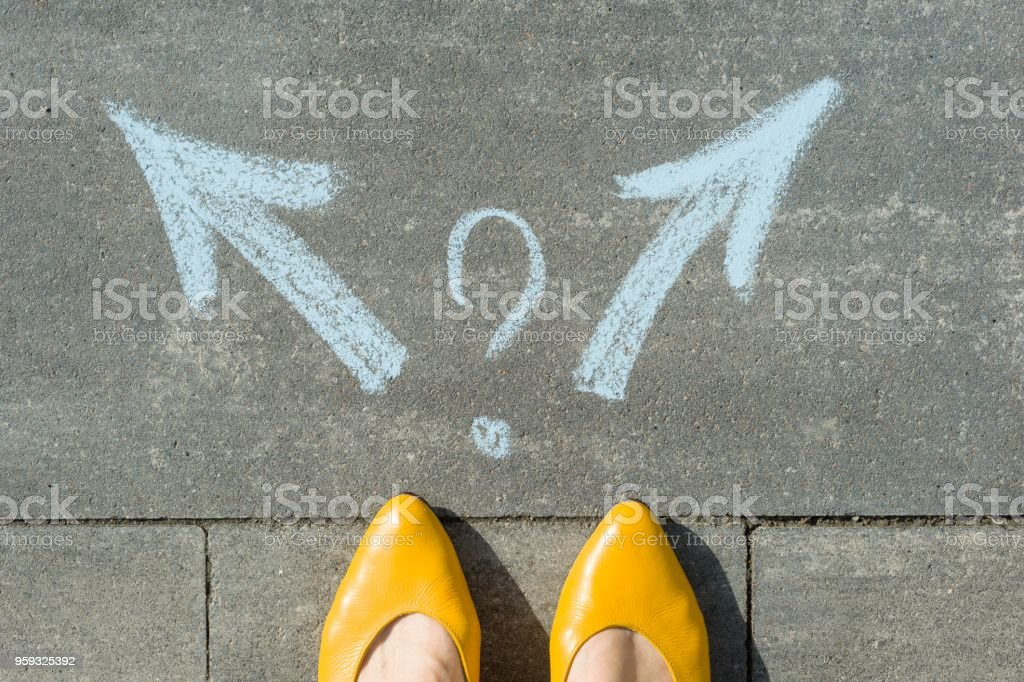 Female legs with 2 arrows and question mark, painted on the asphalt royalty-free stock photo