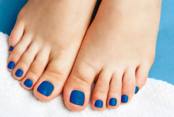 Female legs with pedicure on a white towel close up, concept trend color of the year 2020 Classic Blue. stock photo