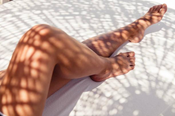Female Legs With Shade Of Straw Umbrella stock photo
