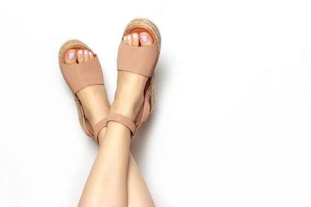 Female legs with white pedicure in summer brown sandals, on a white background, copy of the space stock photo