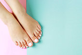 Female legs with white pedicure on a pink and blue background, a top view