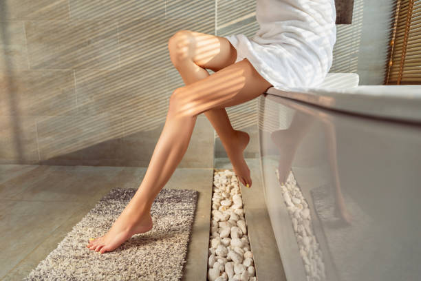 Female legs with yellow nail design in bathroom with sunlight Female legs with yellow nail design in bathroom with sunlight. Summer beauty treatment self care concept. at home laser hair removal stock pictures, royalty-free photos & images
