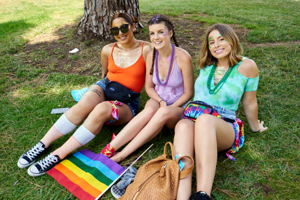 3 female LGBT supporters wearing rainbow colors, lounging under a tree in Balboa Park stock photo