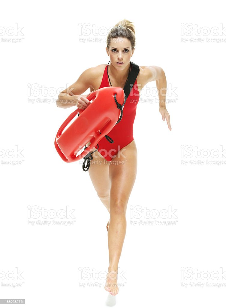 Female lifeguard running with life buoy stock photo