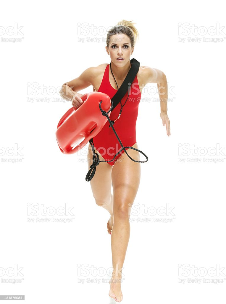 Female lifeguard with life buoy and running stock photo