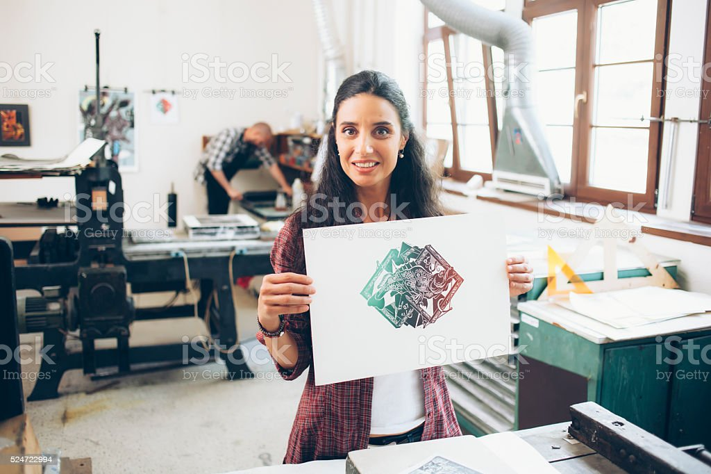 Female lithography worker showing her new artifact stock photo