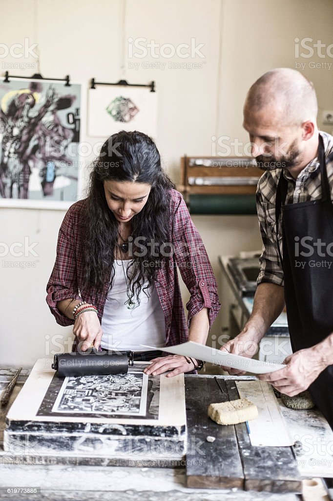 Female lithography workers using printing roller at workshop stock photo