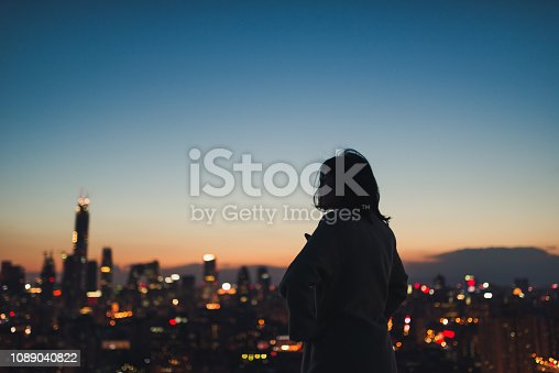 Female looking far away in thought in city