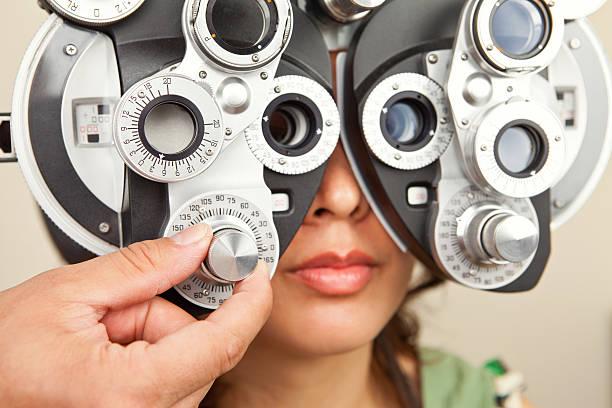 female looking into diopter - lichtbreking stockfoto's en -beelden