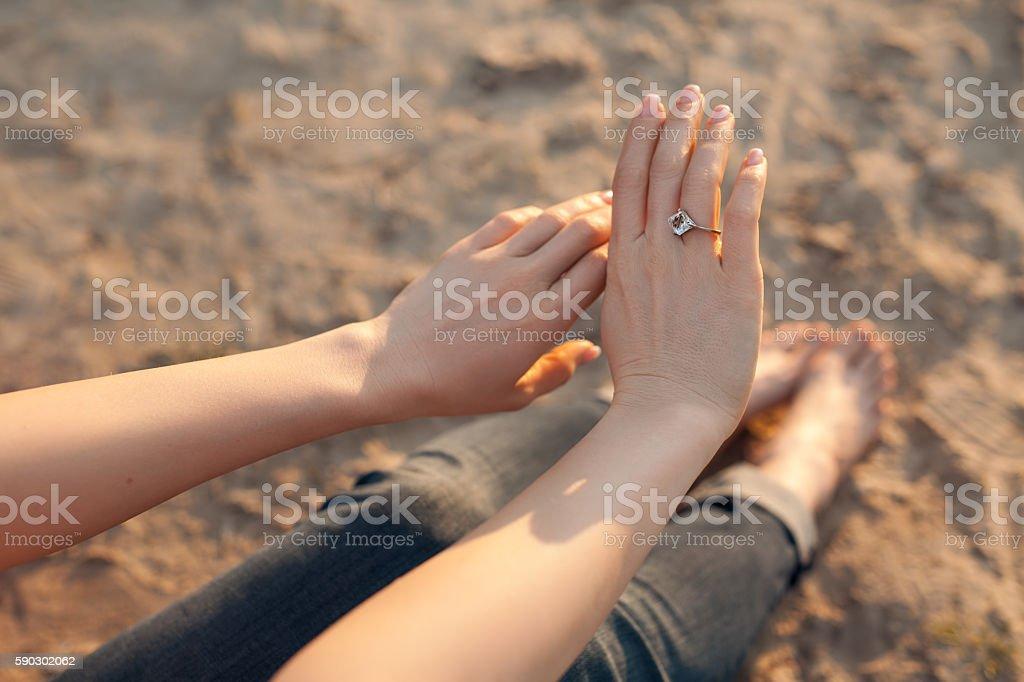 female looks at hand with golden engagement ring; Стоковые фото Стоковая фотография
