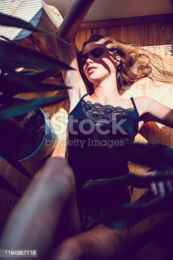 Female Lying Down Beneath Window