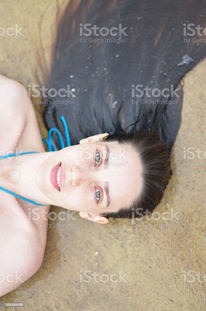 female lying down in sea stock photo