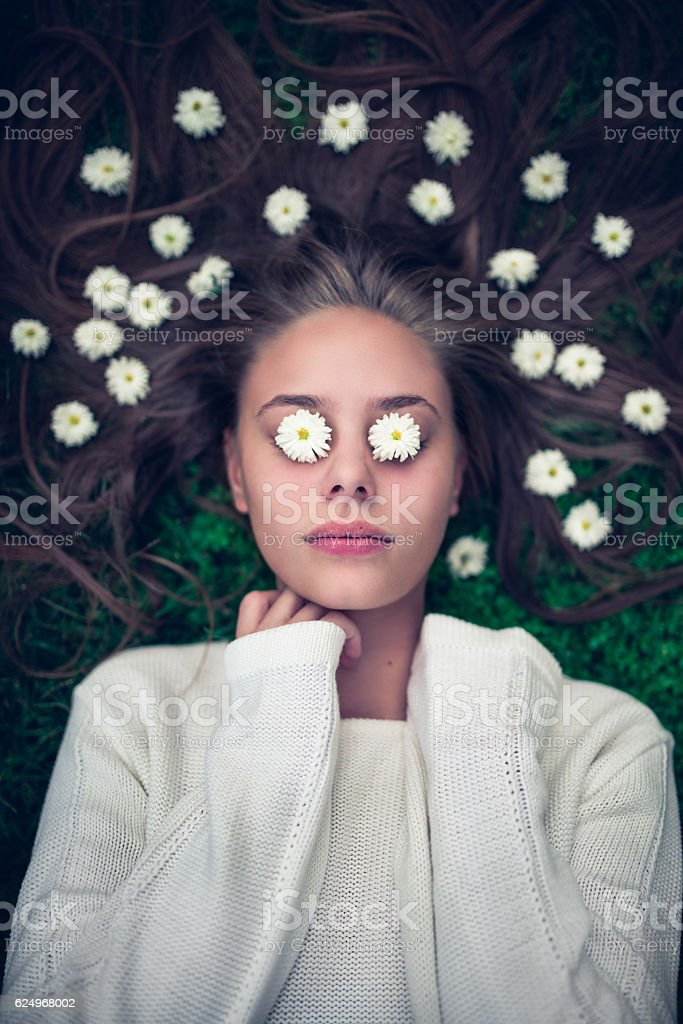 Female Lying on Grass with Daisies in Hair and Eyes stock photo