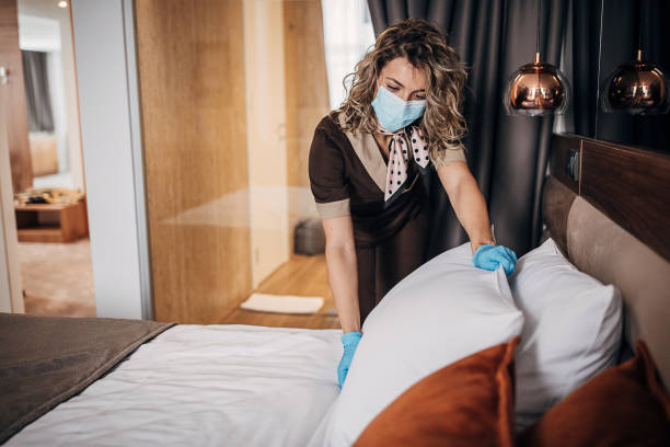 Female maid with medical mask changing bed linen on the bed in a hotel room