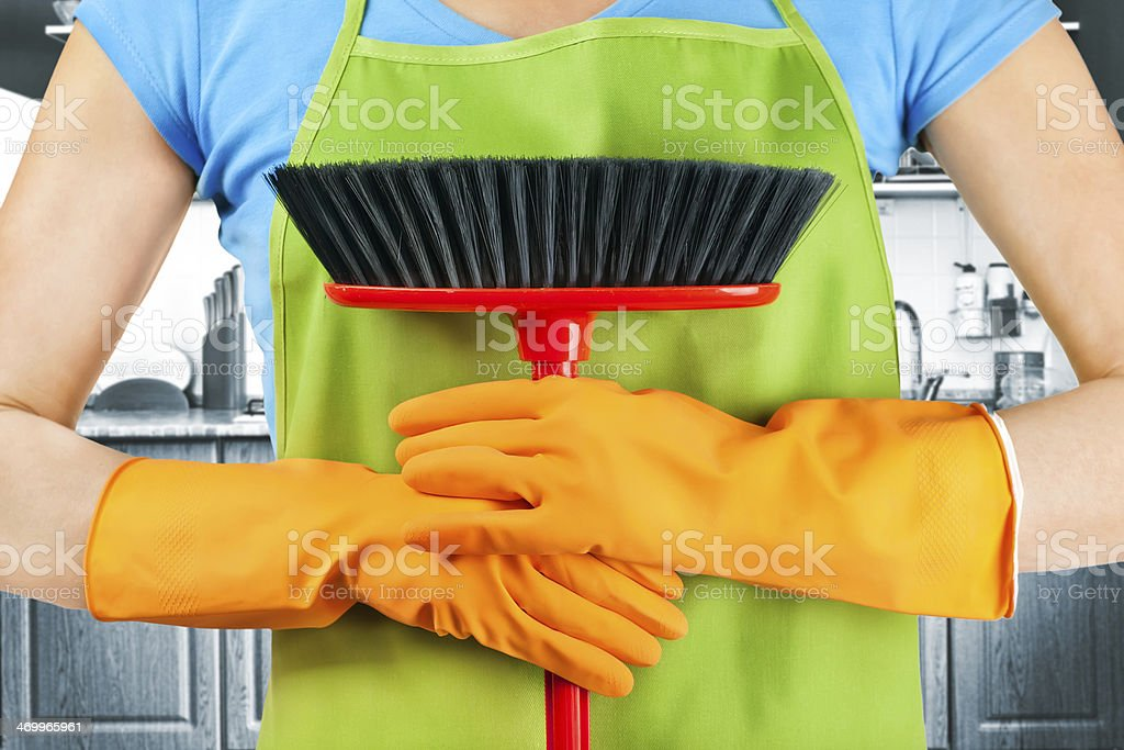 Female maid's hands holding a broom wearing rubber gloves royalty-free stock photo