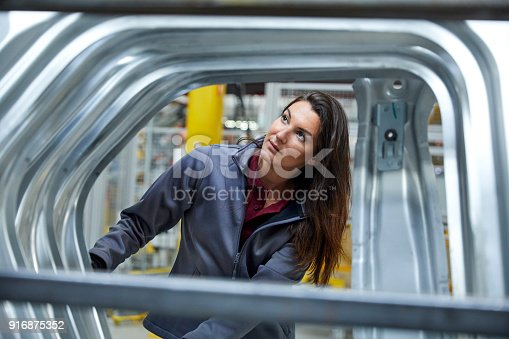 941796726istockphoto Female maintenance engineer examining car chassis 916875352