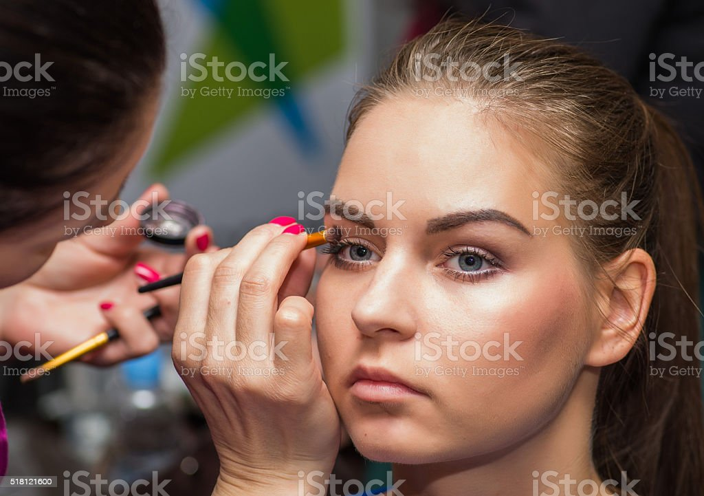 Female make up artist working on model stock photo