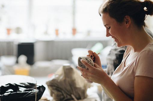 Female maker ceramics creating a shape of ceramic object