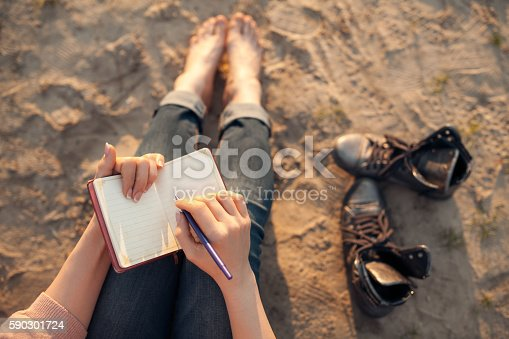 woman writes in diary and sitting on sand;