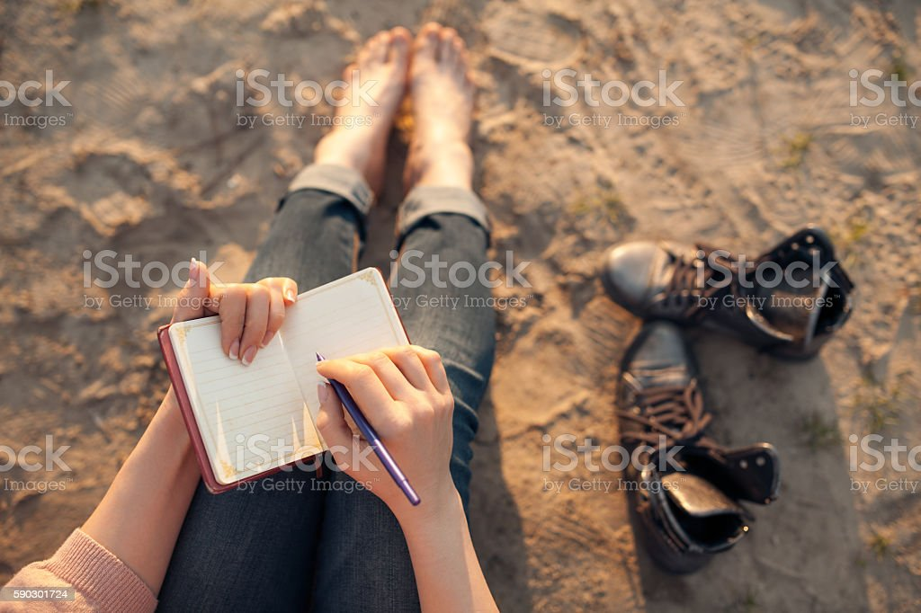 female makes notes and sitting on the beach; stock photo
