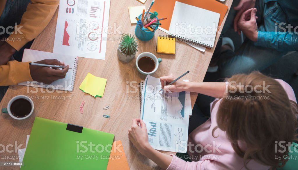 Female making notes on paper at table stock photo