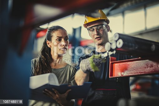 Young female foreman and her manual worker working on paperwork and steel in aluminum mill.