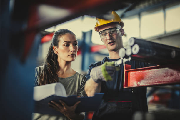 female manager and manual worker analyzing steel in industrial building. - praca w fabryce zdjęcia i obrazy z banku zdjęć