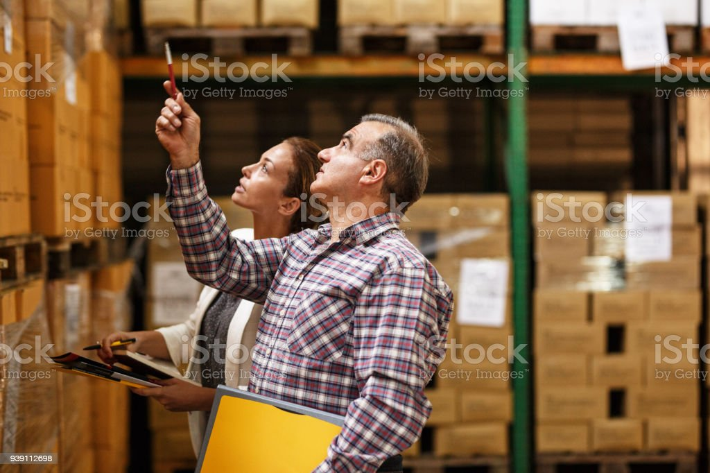 Female manager and warehouse worker checking list and inventory on the shelf in storehouse. stock photo