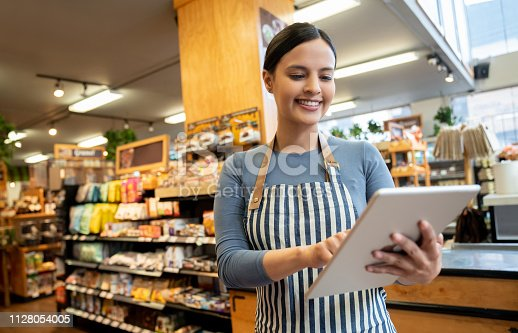 istock Female manager at a supermarket holding tablet smiling 1128054005