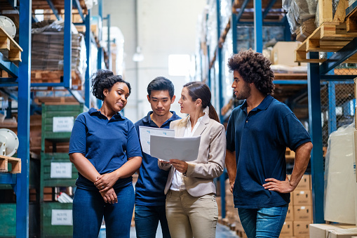 Female manager discussing delivery schedules with staff in warehouse. Female supervisor talking with employees in warehouse.