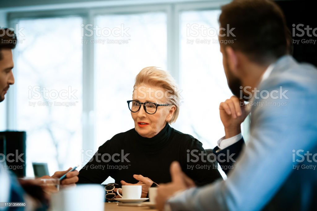 Female manager discussing with male colleagues Confident female senior manager discussing with male colleagues during meeting. Entrepreneurs are planning strategy at workplace. They are at creative office. 30-39 Years Stock Photo
