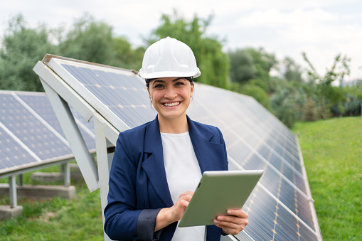 A Female Manager Engineer İn Safety Helmet Checking With Tablet An Operation Of Solar Panel System At Solar Station