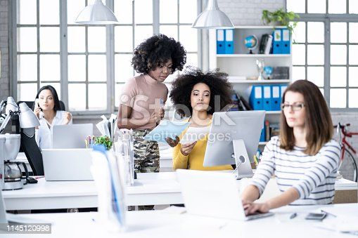 istock Female manager explaning ideas to coworkers in modern office 1145120998