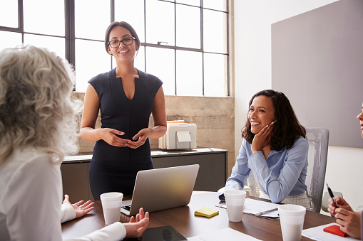Female Manager In Glasses Addressing Businesswomen In Meeting Stock Photo - Download Image Now