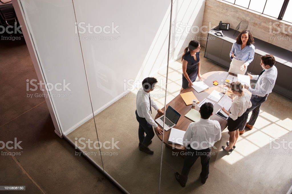 Female manager in team meeting, elevated view through window stock photo