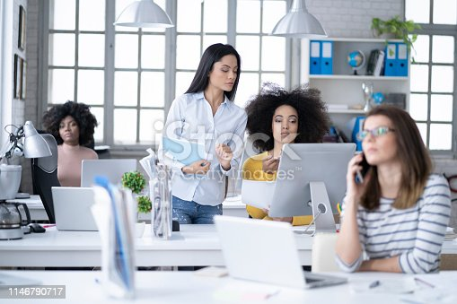 istock Female manager overlooking at wollegues in modern office 1146790717