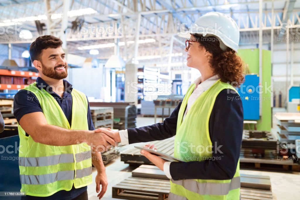 Female manager shaking hand with worker in factory Smiling female manager shaking hand with production worker in factory. Expertise are working in manufacturing company. They are wearing reflective clothing. 20-24 Years Stock Photo