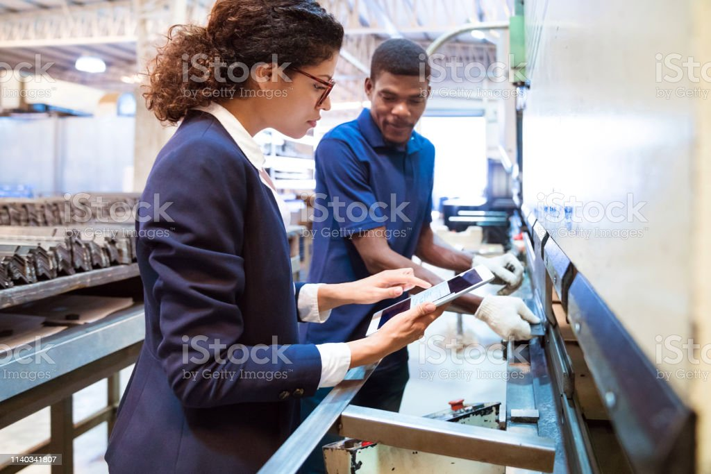 Female manager showing digital tablet to worker Female manager showing digital tablet to production worker. Male engineer is using machinery. Female inspector is on visit in factory. 25-29 Years Stock Photo