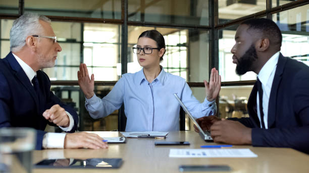 Female manager showing stop sign to arguing workers office, conflict resolution stock photo