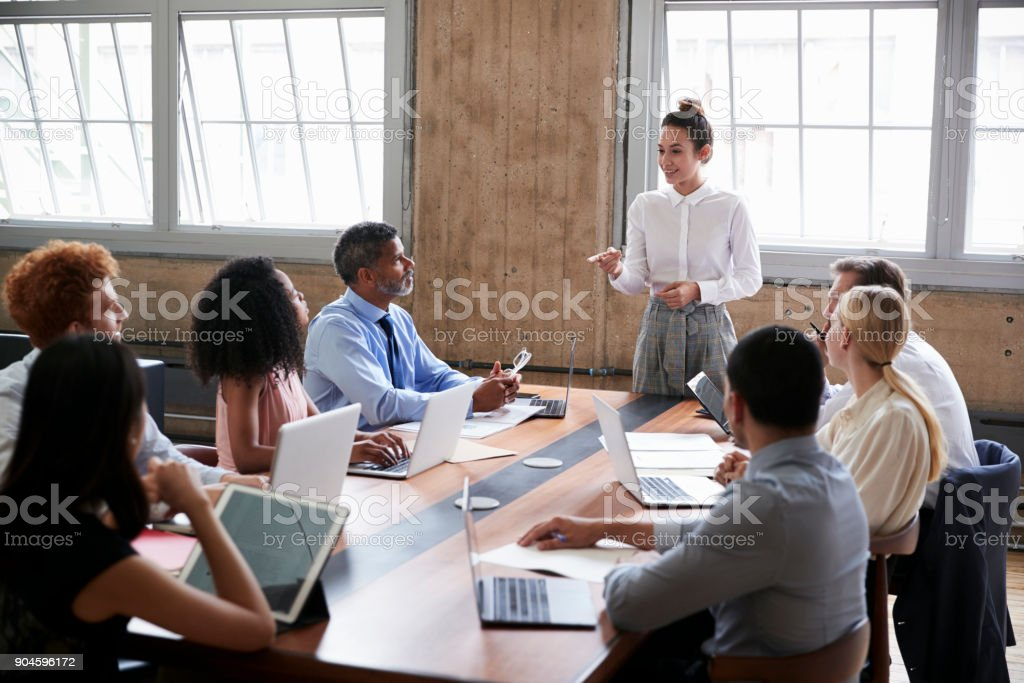 Female manager stands addressing team at board meeting stock photo