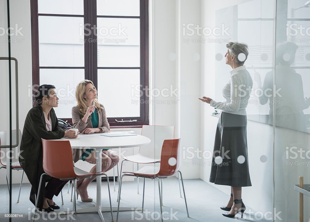 Female manager talking to colleagues behind office partition stock photo